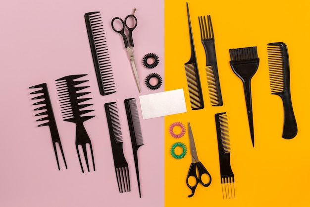 Friseurwerkzeuge auf rosa und gelbem hintergrund mit kopierraum, draufsicht, flache lage. kamm, schere, effilierschere, haarspange. stillleben.