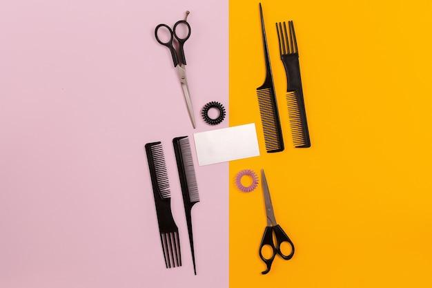 Friseurwerkzeuge auf rosa und orangefarbenem hintergrund mit kopienraum. ansicht von oben. stillleben. attrappe, lehrmodell, simulation. flach legen
