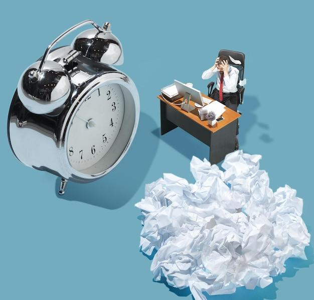 Frist, papierkram. hohe betrachtungswinkel des kreativen modernen büros auf blauem hintergrund - große dinge und kleine arbeiter. büroarbeit, tägliche aufgabe, typische probleme und lifestyle-konzept. collage.