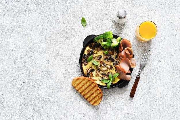 Fritaty scheibe mit pilzen, schinken und brokkoli für ein paar auf einem konkreten hintergrund zum frühstück.