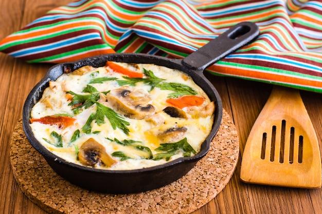 Frittata aus eiern, hähnchen, champignons, zwiebeln, tomaten, käse und petersilie in eisenpfanne