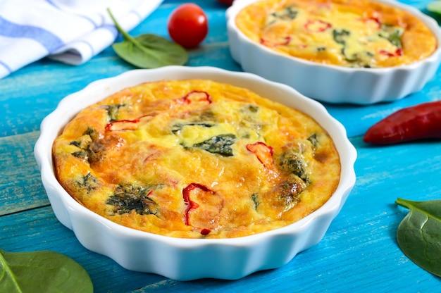 Frittata mit frischem gemüse und spinat. italienisches omelett in keramikformen auf blauem holzhintergrund.