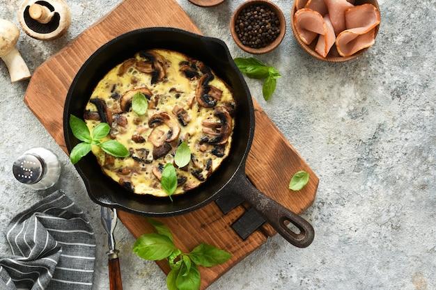 Frittata mit pilzen in einer pfanne mit basilikum auf einem konkreten hintergrund. fritata ist ein italienisches frühstücksgericht.