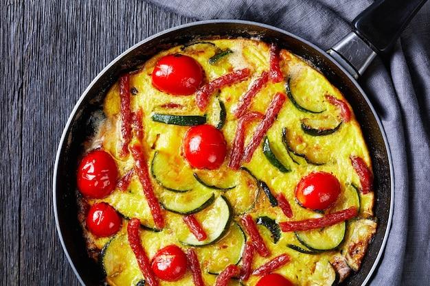 Frittata, omelett mit zucchini, dünne geräucherte würste und tomaten, die eine pfanne auf einem dunklen holztisch füllen, horizontale ansicht von oben, flache lage, nahaufnahme close