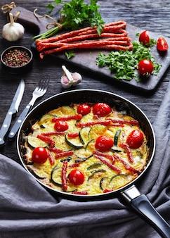 Frittata, omelett mit zucchini, dünne geräucherte würste und tomaten, die eine pfanne auf einem dunklen holztisch mit zutaten an der oberfläche füllen, vertikale ansicht von oben