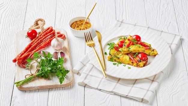 Frittata, omelett mit zucchini, dünne geräucherte würste und tomatenfüllung auf einem weißen teller auf holztisch, horizontale ansicht von oben