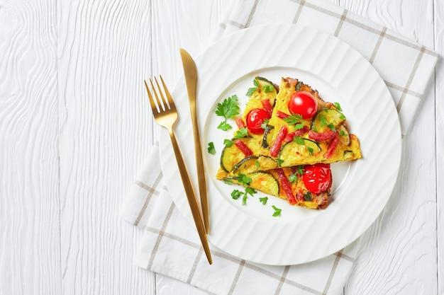Frittata, omelett mit zucchini, dünne geräucherte würste und tomatenfüllung auf weißem teller auf holztisch, horizontale ansicht von oben, flache lage, freier raum