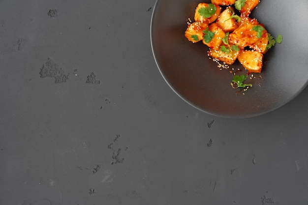 Frittierte auberginen mit kräutern und sesam in schwarzer keramikschale