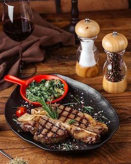 Frittierte fleischscheiben der vorderansicht mit grüns innerhalb des schwarzen tellers mit glas wein auf dem braunen hölzernen schreibtischmahlzeitlebensmittel-fleischessen