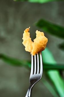 Frittierte garnelen in tempura, auf einer gabel gehackt. nahaufnahme, selektiver fokus. meeresfrüchte