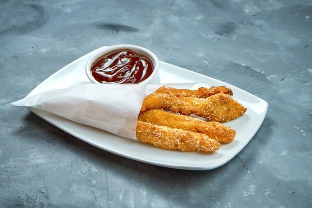 Frittierte hähnchenstangen (streifen) in panade mit roter sauce in einem weißen teller.