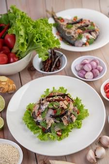 Frittierte makrele mit galangal, pfeffer, minze und roten zwiebeln in einer weißen schale.