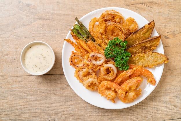 Frittierte meeresfrüchte (garnelen und tintenfisch) mit mischgemüse - ungesunde lebensmittelart
