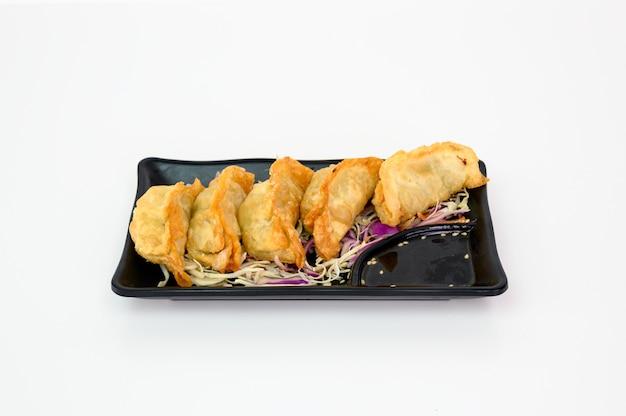 Frittierte schweinefleischknödel mit sojasauce auf teller