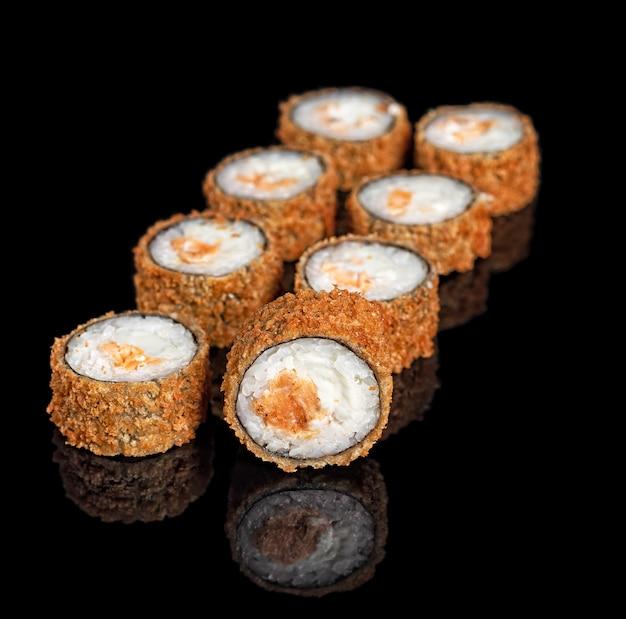 Frittierte sushi-rollen mit lachs und philadelphia-frischkäse. hot crispy tempura set mit reflexion auf schwarzem hintergrund. platz kopieren.