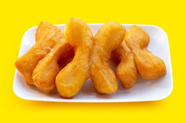 Frittierte teigstangen oder chinesische brotstangen in weißer platte auf gelbem hintergrund.