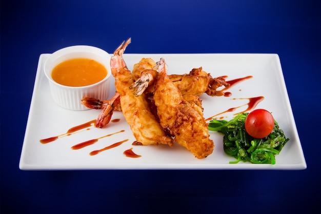 Frittierte tigergarnelen im teig serviert mit süß-saurer sauce, nori-algen und kirschtomaten auf einem rechteckigen teller.