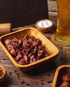 Frittierte wurst mit salz und glas bier auf dem tisch