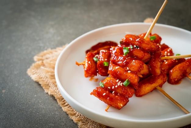 Frittierter koreanischer reiskuchen (tteokbokki) am spieß mit scharfer sauce - koreanische küche