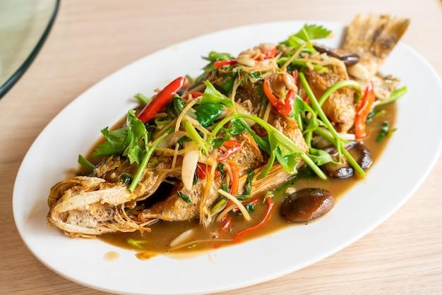 Frittierter wolfsbarschfisch mit süßer sauce und zutaten - asiatische küche