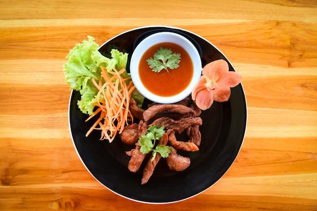 Frittiertes rindfleisch oder schweinefleisch mit soße und frischgemüse auf platte in der draufsicht des holztischs. thailändisches gebratenes sonnengetrocknetes rindfleisch-asiatslebensmittel