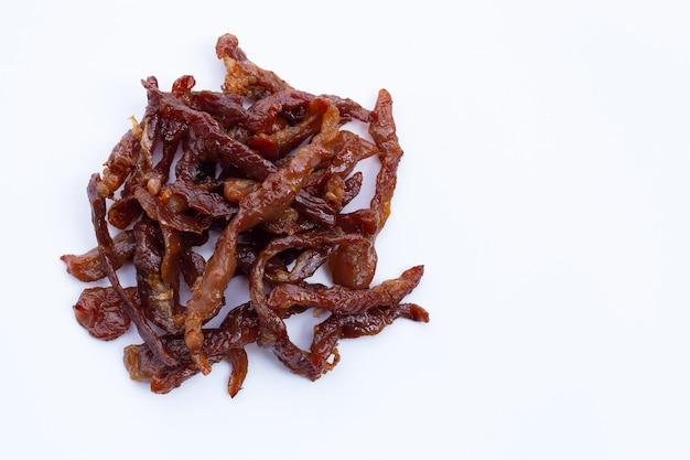 Frittiertes sonnengetrocknetes schweinefleisch auf weißer oberfläche.
