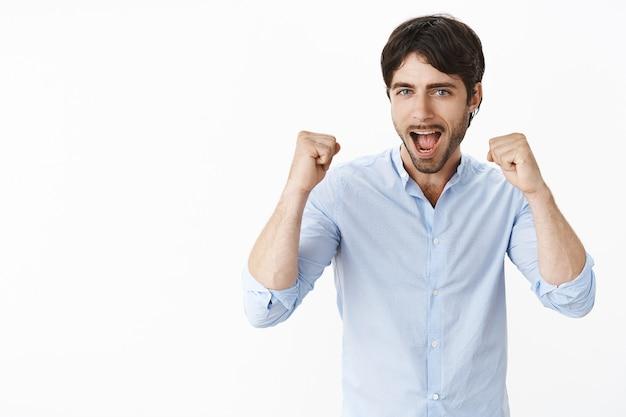 Fröhlich aufgeregter, gutaussehender unternehmer, der jubelt und triumphiert, ja schreit und geballte fäuste in sieg- und erfolgsgeste hebt und sich über gute nachrichten freut, die über grauer wand erfreut stehen