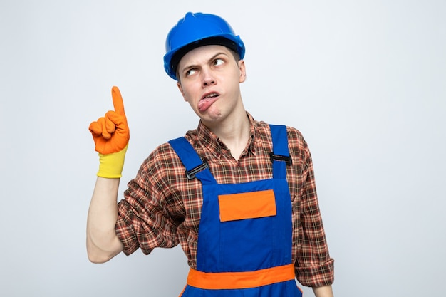 Fröhlich aussehende seite mit zunge zeigt auf junge männliche baumeister, die uniform mit handschuhen tragen