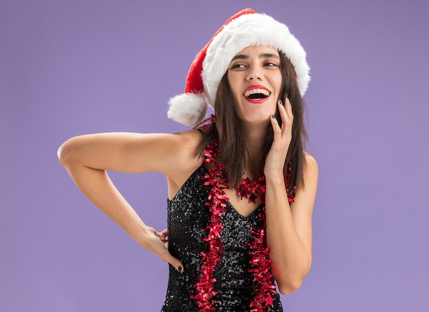 Fröhlich aussehendes junges schönes mädchen mit weihnachtsmütze mit girlande am hals, das die hände auf die hüfte und den kopf legt, isoliert auf violettem hintergrund