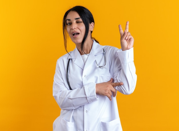 Fröhlich blinzelte junge ärztin, die ein medizinisches gewand mit stethoskop trägt, das eine friedensgeste einzeln auf gelber wand zeigt