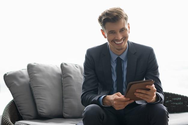 Fröhlich erfolgreicher junger mann mit dem tablet-computer