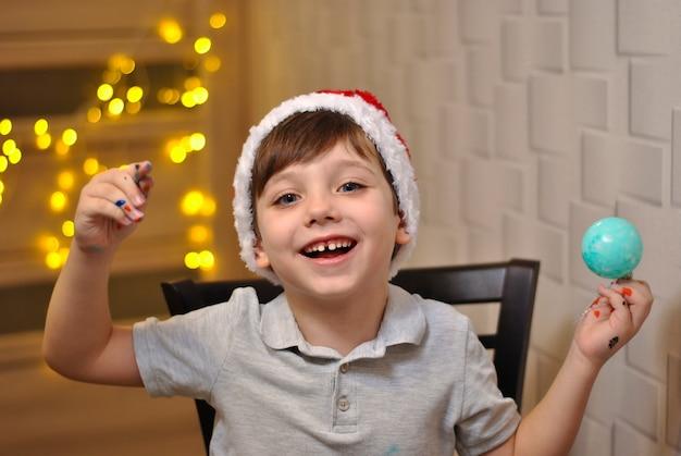 Fröhlich glücklich lächelnder kleiner junge malt weihnachtskugeln in rotem und weißem flauschigem weihnachtshut