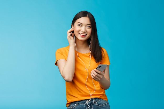 Fröhlich gut aussehende asiatische frau schaut erfreut hoch, hält smartphone-plug-in-kopfhörer lächelnd zufrieden gute klangqualität, genießen sie das hören von musikständer blauem hintergrund begeistert optimistisch