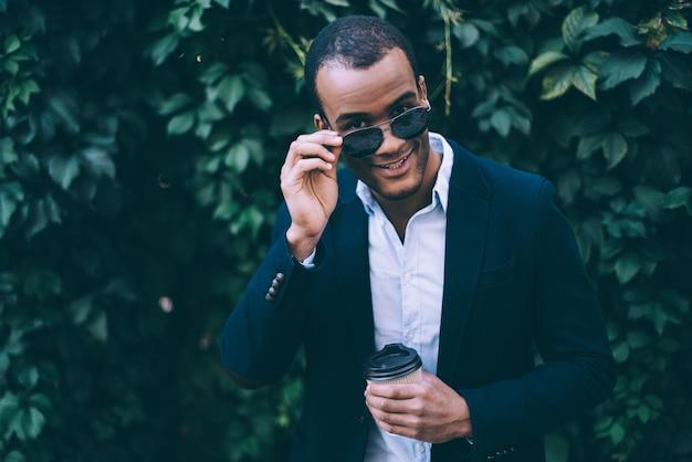 Fröhlich gutaussehend. hübscher junger afrikanischer mann, der seine sonnenbrille justiert und zu ihnen lächelt, während er eine kaffeetasse hält und draußen vor grünem pflanzenhintergrund steht