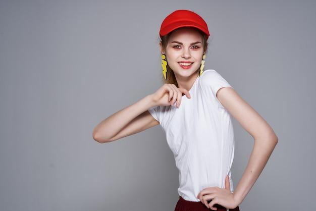 Fröhlich hübsches mädchen rote mütze make-up ohrringe glamour isolierten hintergrund. foto in hoher qualität