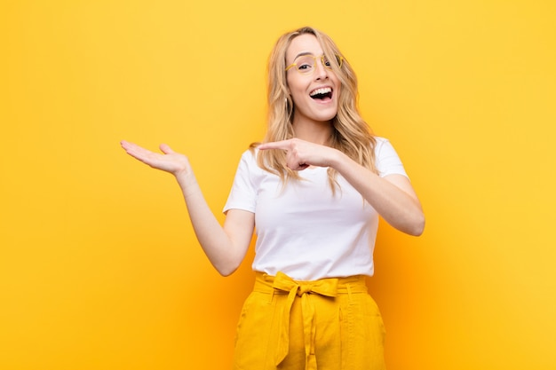 Fröhlich lächeln und zeigen, um platz auf der handfläche an der seite zu kopieren, ein objekt zu zeigen oder zu bewerben