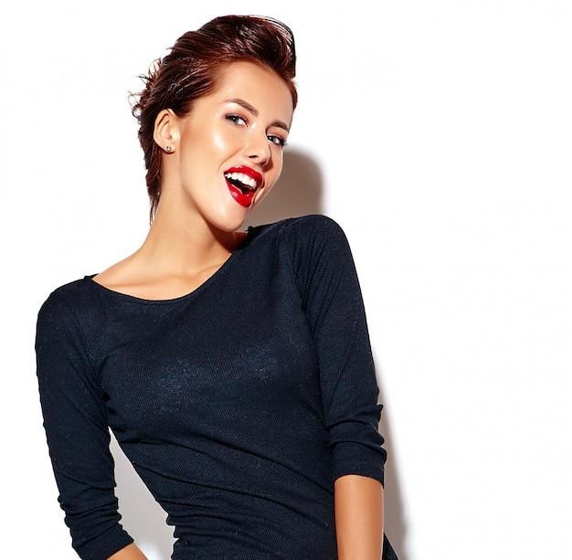 Fröhlich lächelnd zwinkert mode frau verrückt in lässig schwarzer kleidung mit roten lippen auf weiße wand