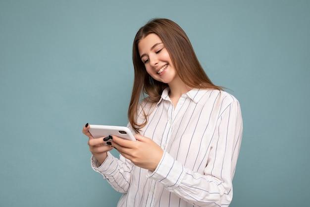 Fröhlich lächelnde attraktive junge blonde frau mit lässigem weißem hemd isoliert über blauer hintergrundwand, die smartphone hält und online-spiele mit blick auf den gadjet-bildschirm spielt. Premium Fotos