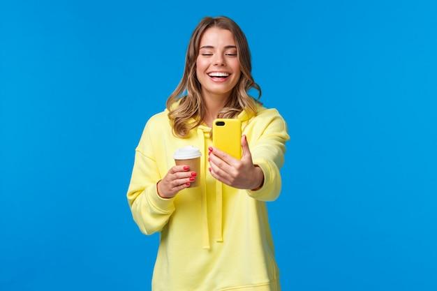 Fröhlich lächelnde blonde blonde kaukasische bloggerin video aufnehmen oder selfie auf ihr handy nehmen, lachen und grinsen, während sie eine tasse kaffee zum mitnehmen halten, blaue wand stehen