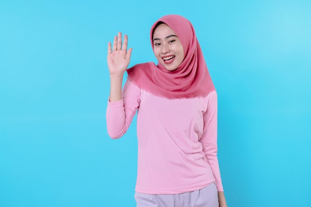 Fröhlich lächelnde frau mit attraktivem aussehen und einem rosafarbenen t-shirt mit hijab, das ein lächeln zeigt