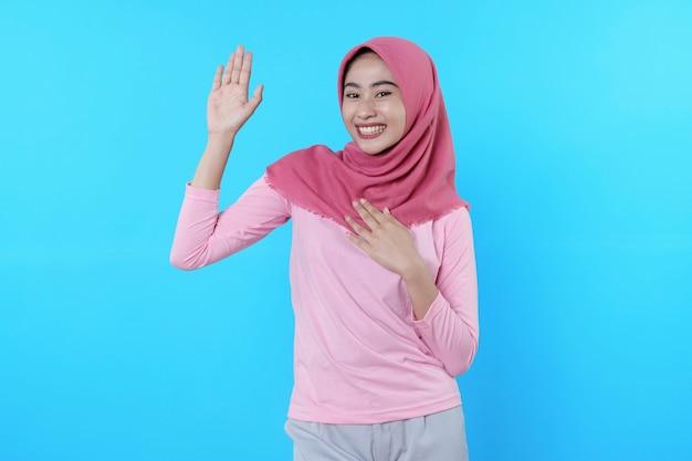 Fröhlich lächelnde frau mit attraktivem aussehen und tragen von hijab, rosa t-shirt mit spruch sagen hallo lächeln gute laune