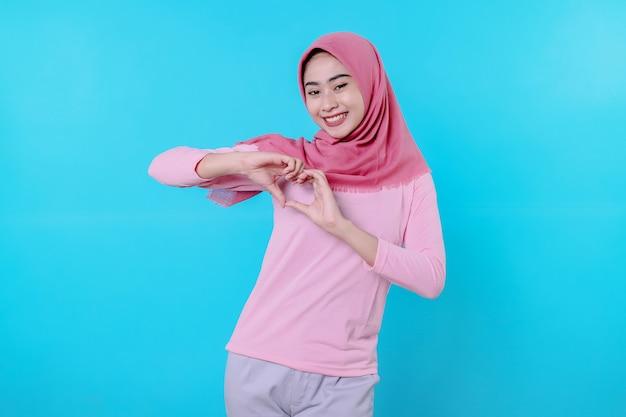 Fröhlich lächelnde frau mit attraktivem aussehen und tragen von hijab, rosa t-shirt zeigt liebeslächeln gute laune