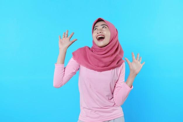 Fröhlich lächelnde frau mit attraktivem aussehen und tragendem hijab, rosa t-shirt, das gute laune zeigt