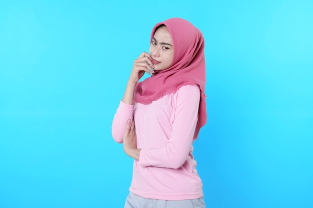 Fröhlich lächelnde frau mit attraktivem aussehen und tragendem hijab, rosa t-shirt mit stillem ausdruck