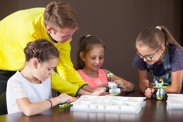 Fröhlich lächelnde kinder bauen einen konstruktor.