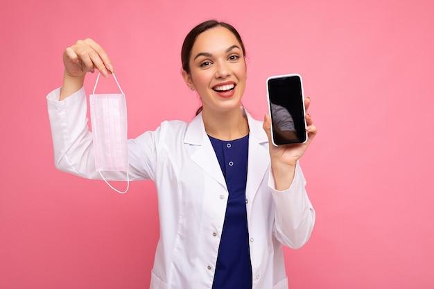 Fröhlich lächelnde krankenschwester mit weißem kittel mit maske, die modernes mobiltelefon isoliert über rosafarbenem hintergrund mit blick auf die kamera zeigt