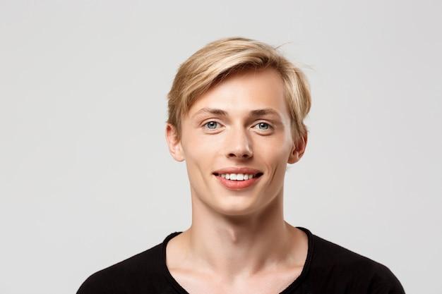 Fröhlich lächelnder blonder hübscher junger mann, der schwarzes t-shirt auf grauer wand trägt