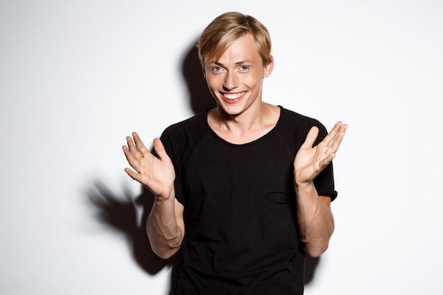 Fröhlich lächelnder blonder hübscher junger mann, der schwarzes t-shirt trägt, das hände auf weißer wand klatscht