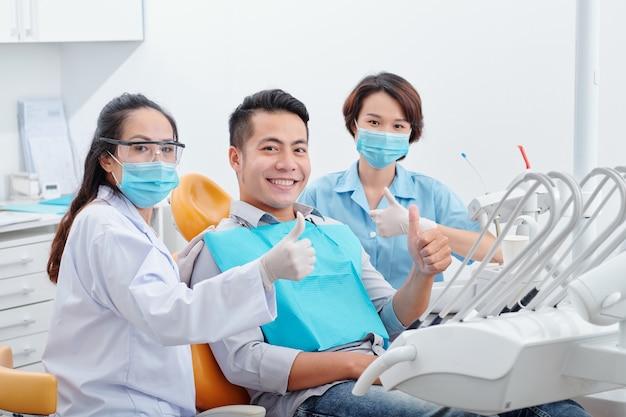 Fröhlich lächelnder, gutaussehender asiatischer mann, sein zahnarzt und seine assistentin in medizinischen masken, die nach abschluss der behandlung daumen nach oben zeigen