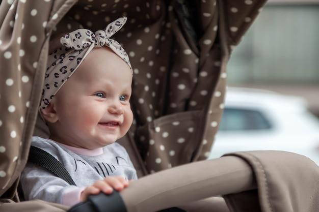 Fröhlich lächelndes emotionales acht monate altes blauäugiges mädchen sitzt im kinderwagen auf einem spaziergang und wartet auf mama. kleines und süßes baby mit stirnband auf dem kopf, das im kinderwagen sitzt. konzept der richtigen erziehung und kindheit